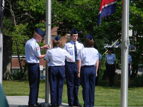 Four service members raising the flag