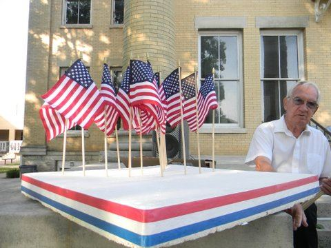 Man standing beside mini-flags ina a styrofoam holder