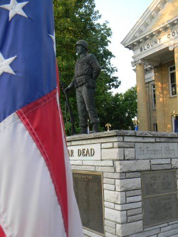 Image of American flag upclose, with war memorial in background
