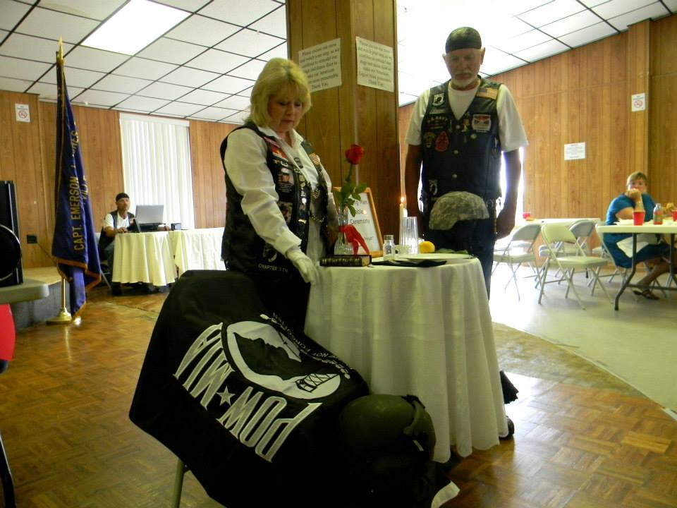 Man and woman standing beside the POW-MIA honorary table