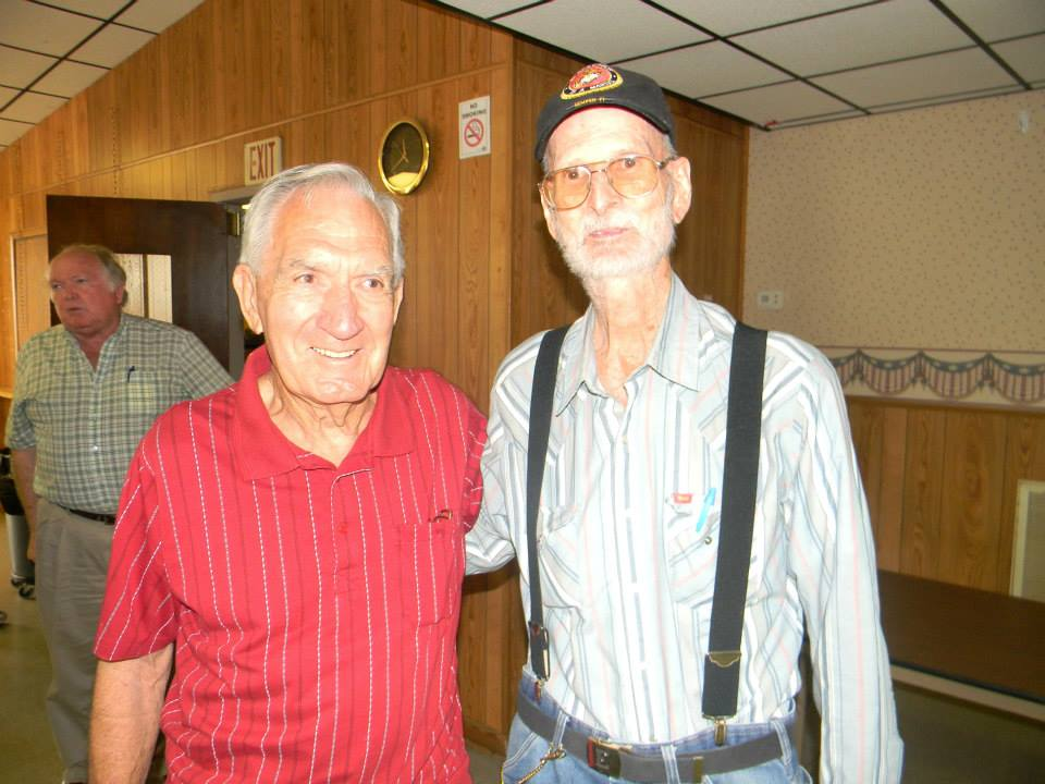Man in red shirt, standing and smiling beside man in blue striped shirt and hat