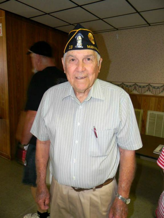 Man in light blue shirt, wearing Korean War veteran hat, standing and smiling