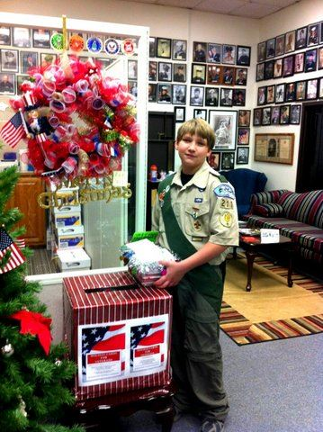 Boy Scout at post box decorated for veterans