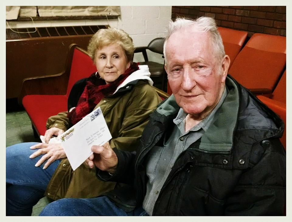 Woman sits beside man who is holding up a card