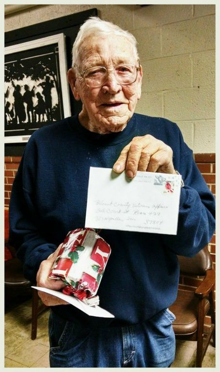 Veteran holds a wrapped present and an envelope, standing and smiling at camera
