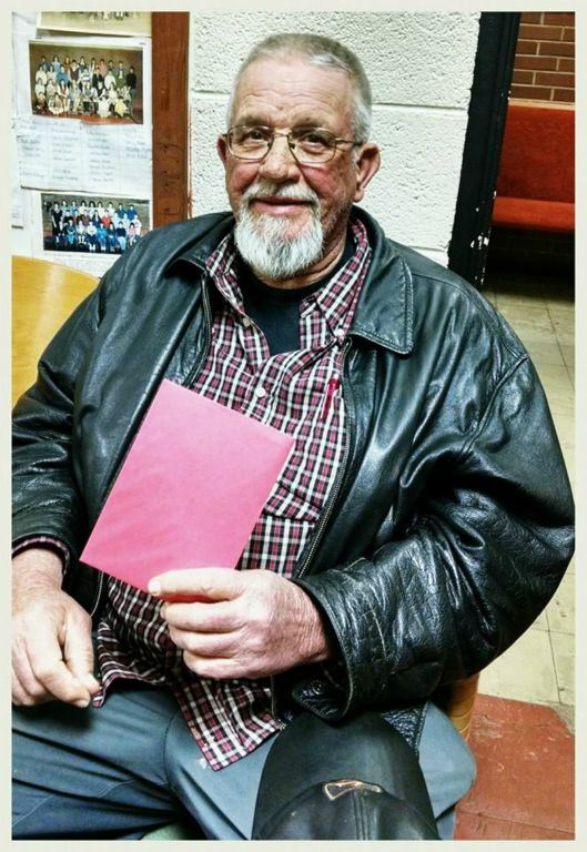 Veteran in black leather jacket smiles while sitting and holding red envelope