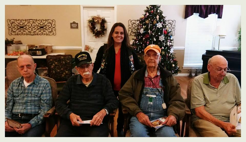 Sitting in a row in front of a Christmas tree are four veterans with cards, and one smiling standing woman behind them