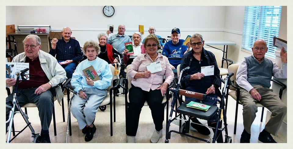 Picture of group- three lines of rowed chairs with veterans sitting, smiling, and holding up cards