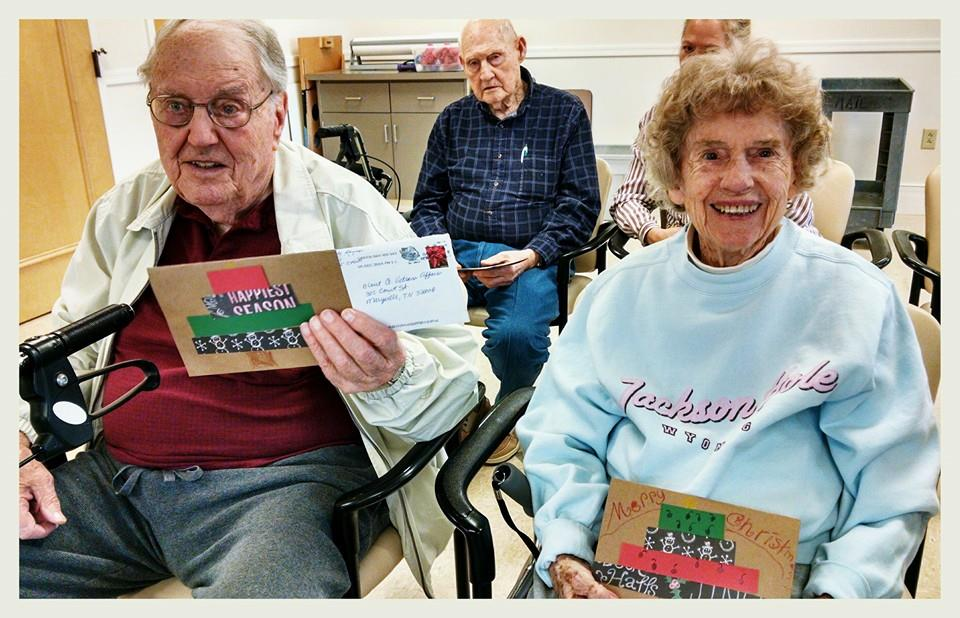 Man and woman sitting beside each other hold cards and smile towards the camera