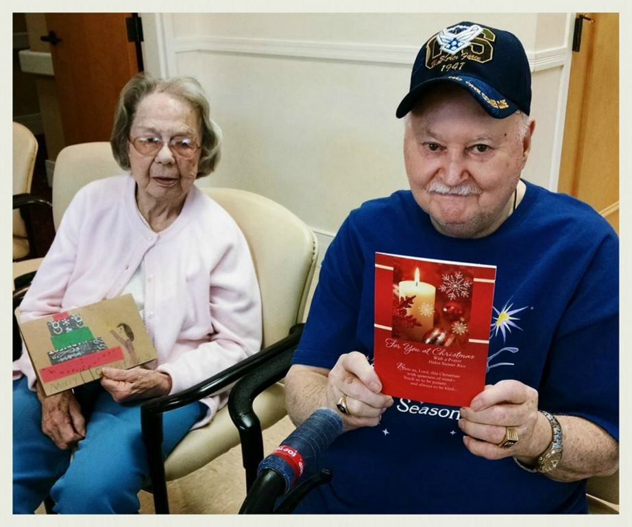 One woman and one man veteran hold up their holiday cards for the photographer