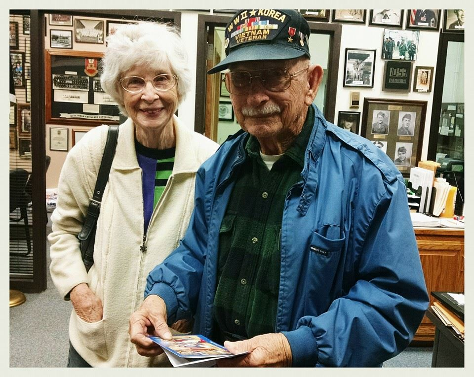 Smiling veteran in blue receives cards, with friendly lady beside him