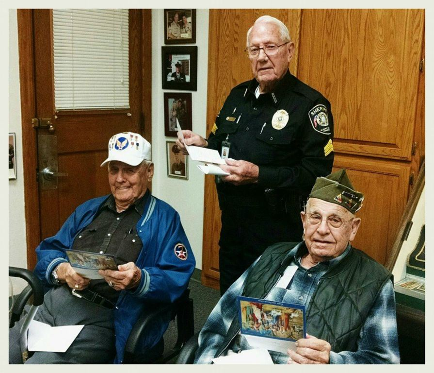 Two sitting veterans, and one standing Sheriff (also a veteran) all three with cards