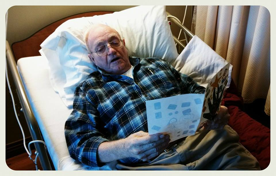 Relaxing veteran, wearign plaid and with glasses, reads card with a handprint on the front