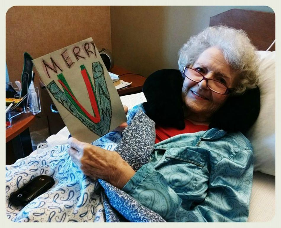 Woman veteran relaxes in bed with enck pillow, smiling at camera, holding a card