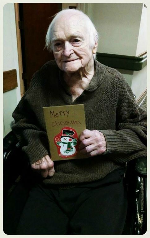Veteran in wheelchair holds snowman card up, smiling at camera