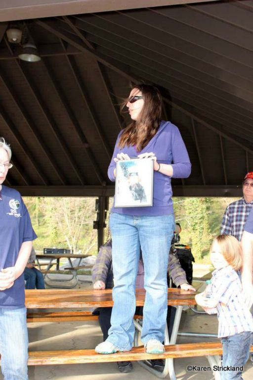 Woman stands on picnic bench holding framed picture of marine, speaking to crowd
