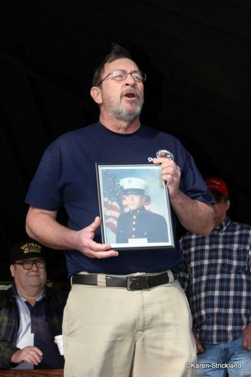 Man in blue shirt holds framed image of marine while speaking