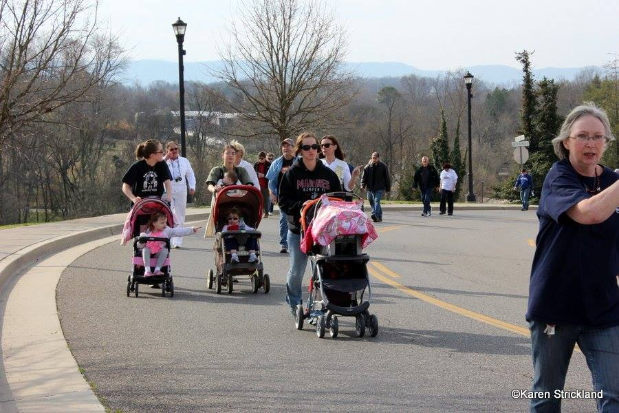 Walkers walk up hill, women with strollers