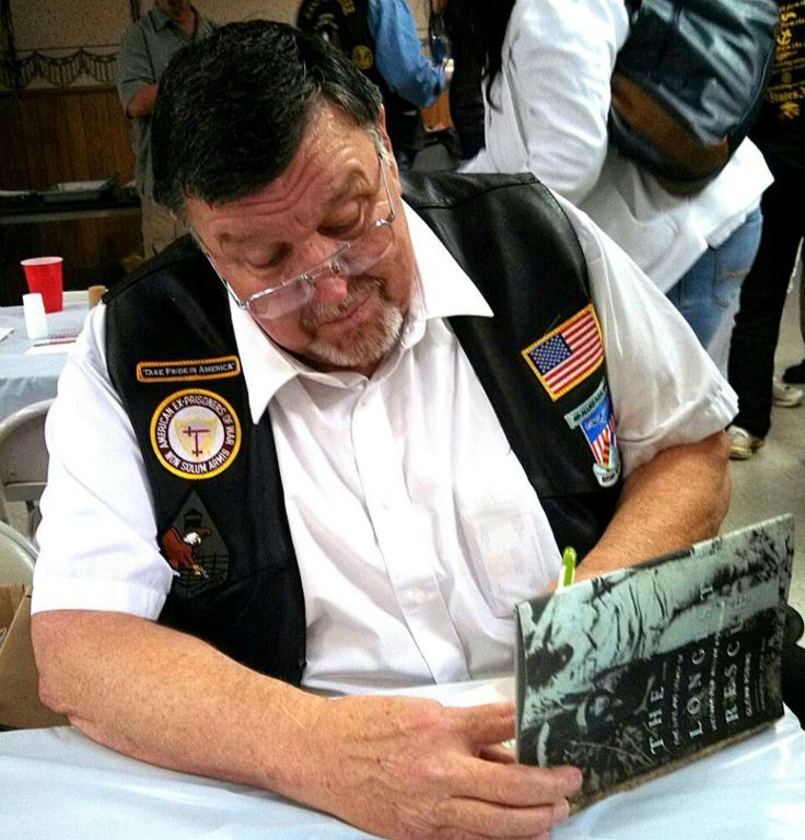 Man signs copy of The Longest Rescue book, sitting at table