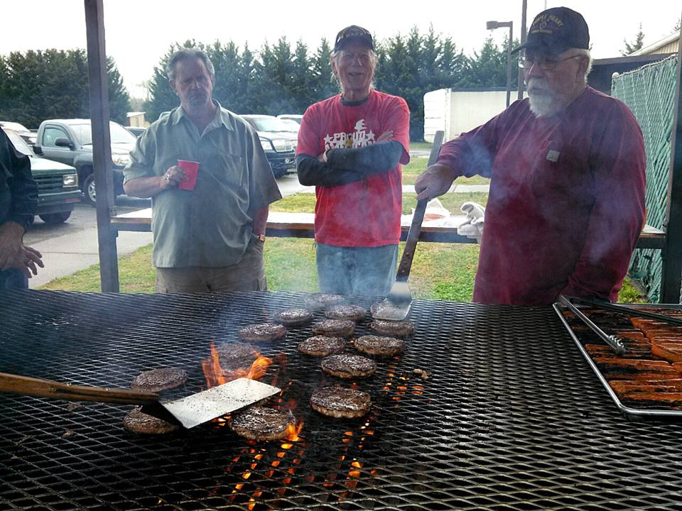 Three men stand around large grill with burgers and hotdogs cooking