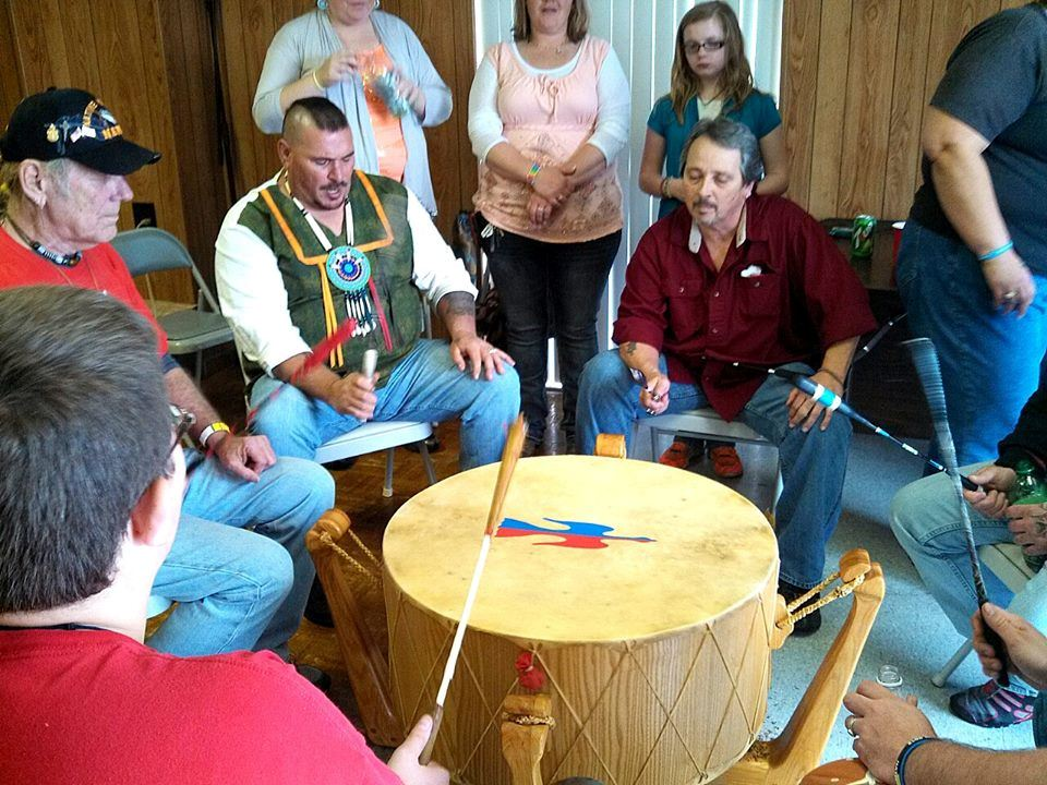Man wearing Native American beads plays a large drum with others in circle
