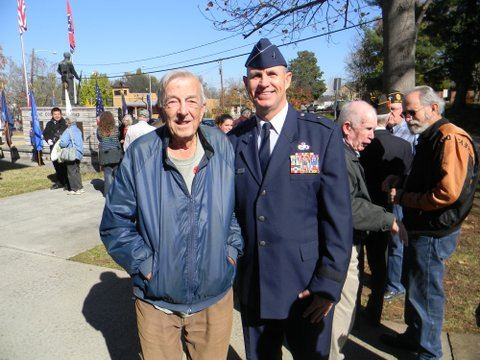 Older man in blue jacket stands with man in uniform, both smiling for camera