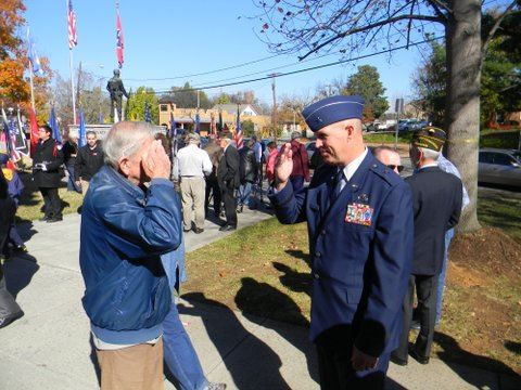 Older man in blue jacket stands with man in uniform, both salute each other
