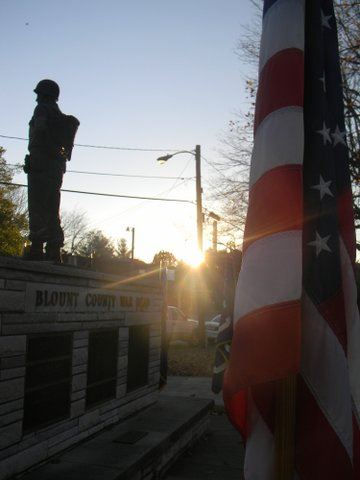 Image of American  flag with the Blount County War Dead memorial soldier statue in background