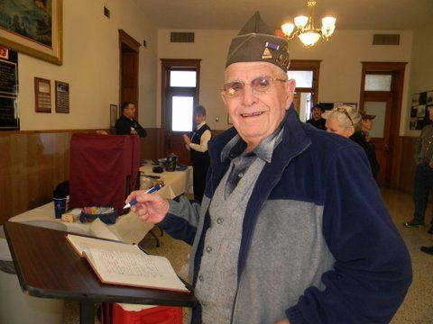 Veteran smiles at camera with pen in hand about to sign guestbook in Court house