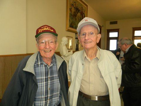 Two men smile, standing beside each other, one has arm on other's shoulder, one in khaki, one in blue plaid, both in hats