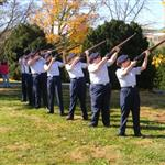 Cadets aim firearms, standing on lawn, wearing blue uniforms