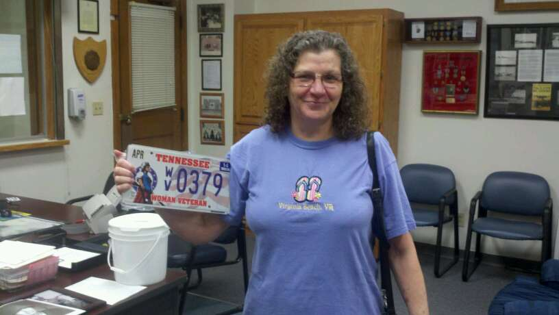 Woman in purple shirt proudly holds up Tennesee license plate with Woman Veteran vanity