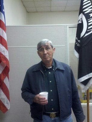 Man stands between American flag and POW-MIA flag, holding coffee cup and looking into camera