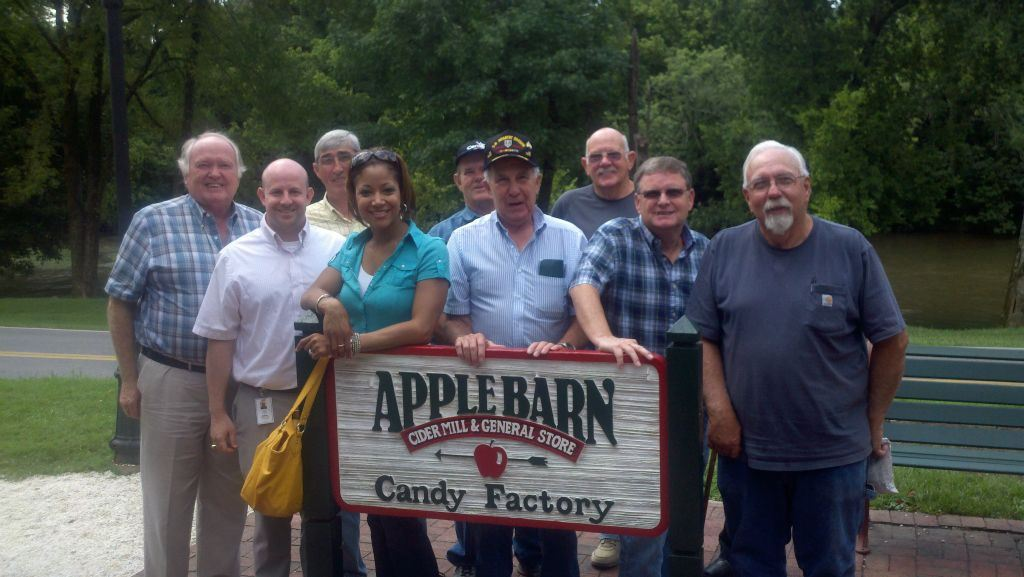 Nine people stand behind wooden siagn with text Applebarn Candy Factory