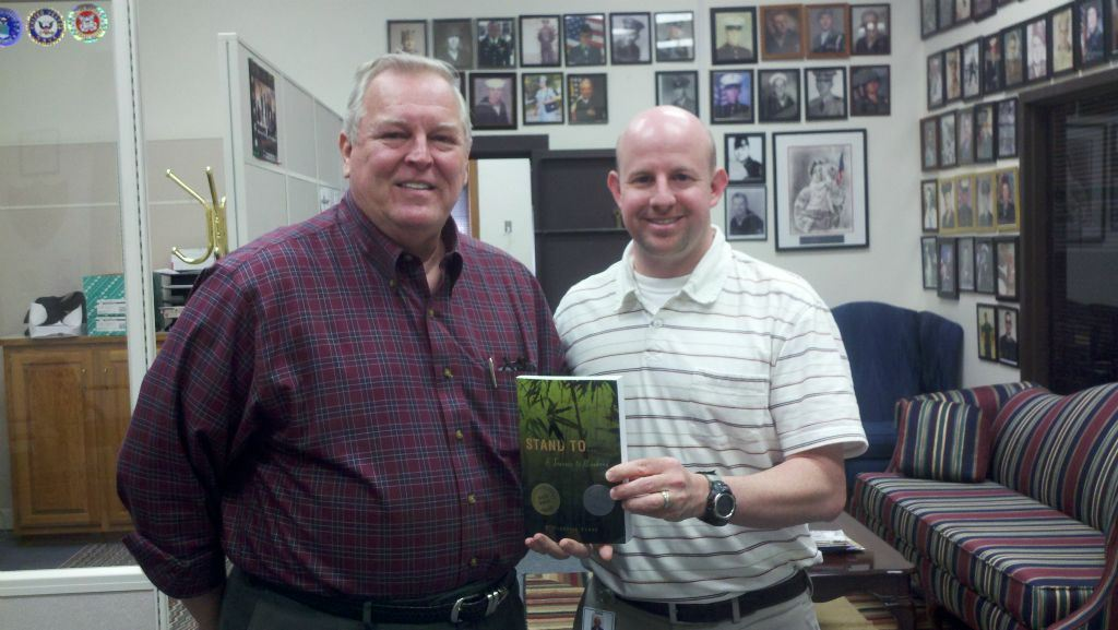 Man in red plaid stands with Nathan Weinbaum in office, Nathan is holding book titled Stand To