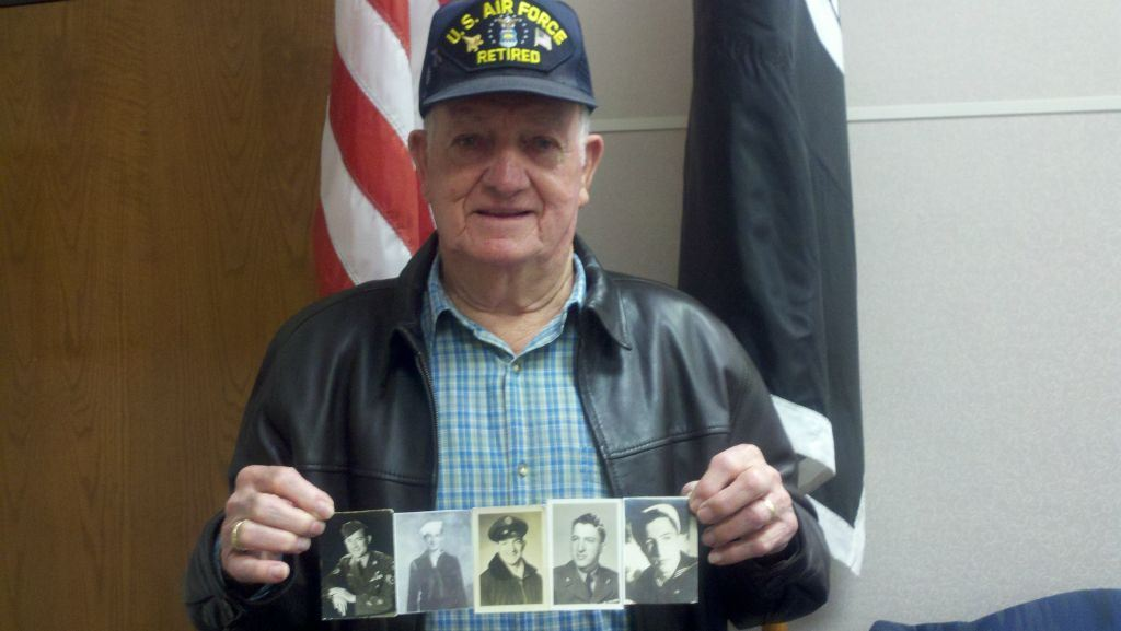 Man wearing US Air Force Retired and blue plaid shirt holds up collage of sepia and black and white photos