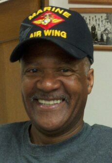 Up lose image of smiling man, lokoing into camera, wearing black hat that says Marine Air Wing
