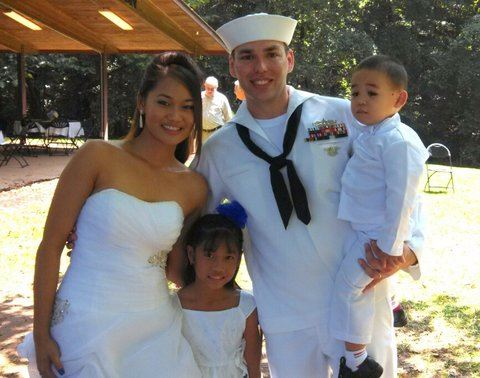 Image of bride in dress, with little girl and navyman in whites holding youg boy