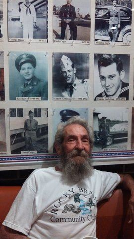Man in white shirt with beard sits on cuoch, with vintage military photogrpahs behind him