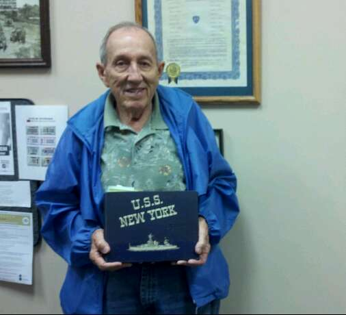 Man wearing blue coat looks smiling into camera, holding USS New York book in hands