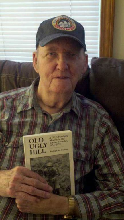 Man in plaid shirt sitting on sofa, smiles into camera holding up book with title Old Ugly Hill