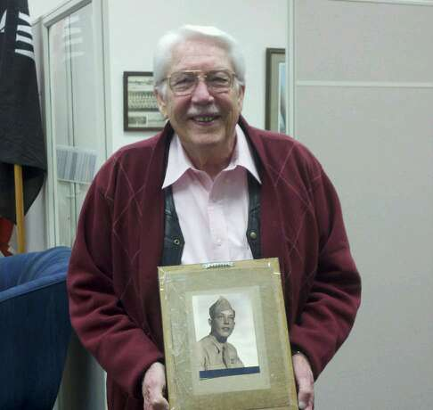 Image of veteran wearing glasses and maroon sweater, holding up black and white picture of young soldier