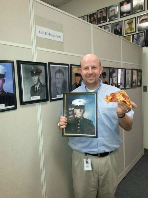 Nathan Weinbaum stands at the Killed in Action gallery wall, holding portrait of a marine and a slice of pizza