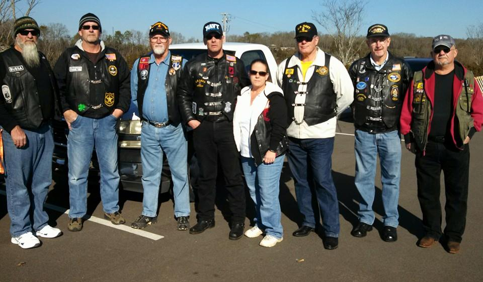 Eight people standing in parking lot, looking into camera, some are wearing black leather biker gear, most with veterans hats