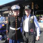 Two men side hug in parking lot in front of purple motorcycle, one in dress Marine uniform and one in biker leather vest